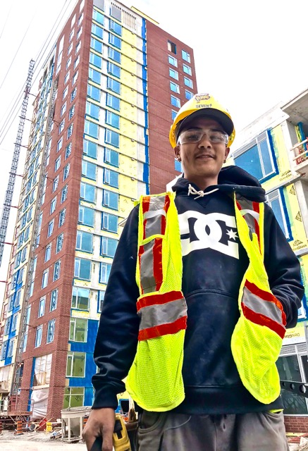 Photo of a young man in construction wear standing in front of a high rise building.