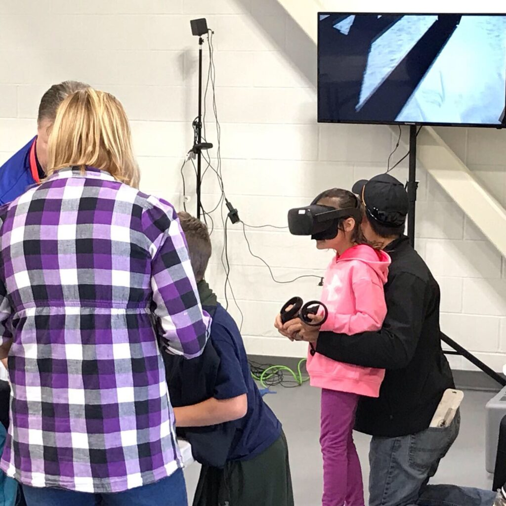 A girl in a pink sweatshirt uses a virtual reality headset.