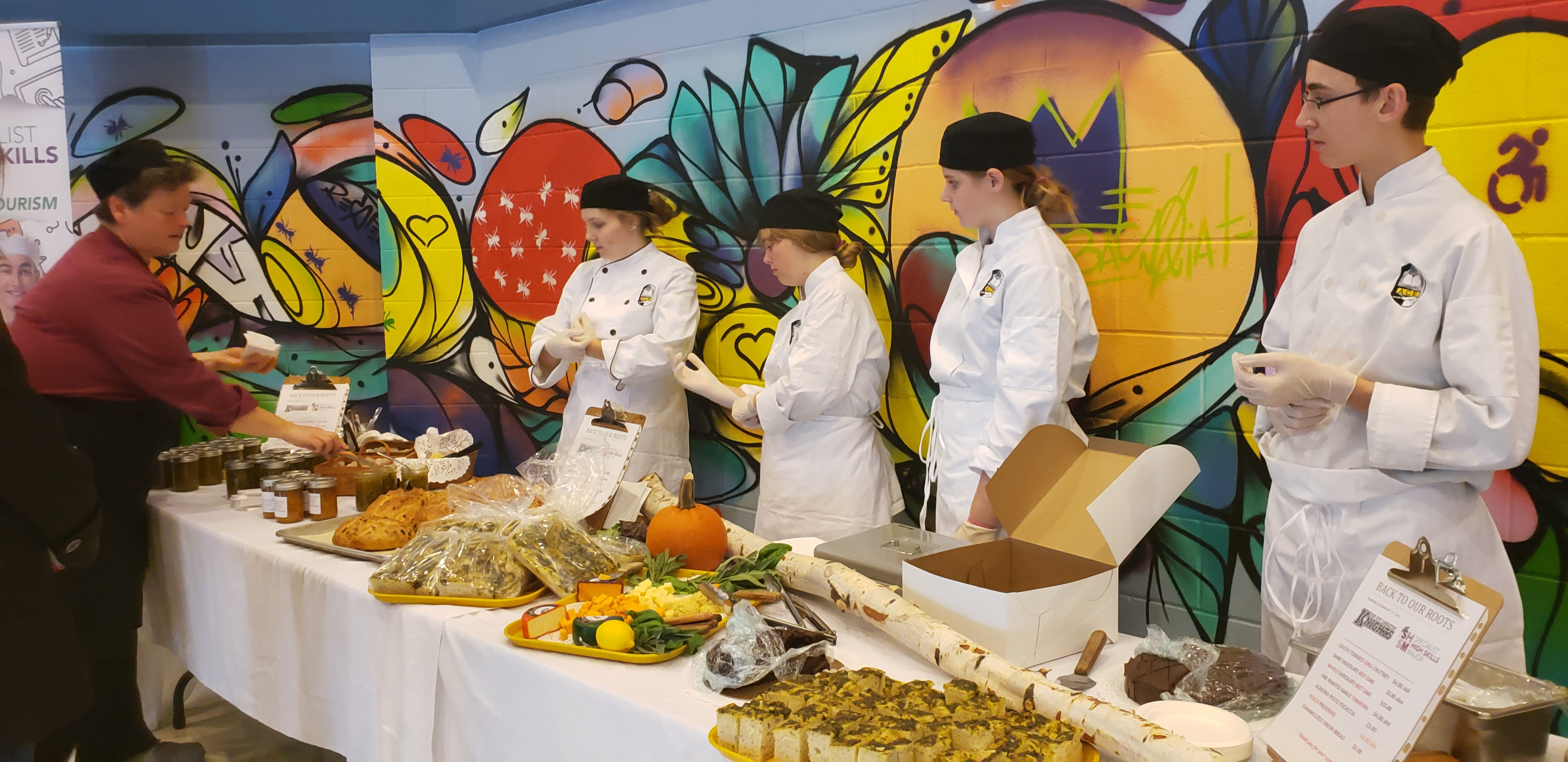 Four students wearing chef uniforms ready to serve food they have prepared.
