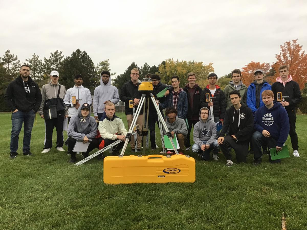 A group of students gathered around surveying equipment.