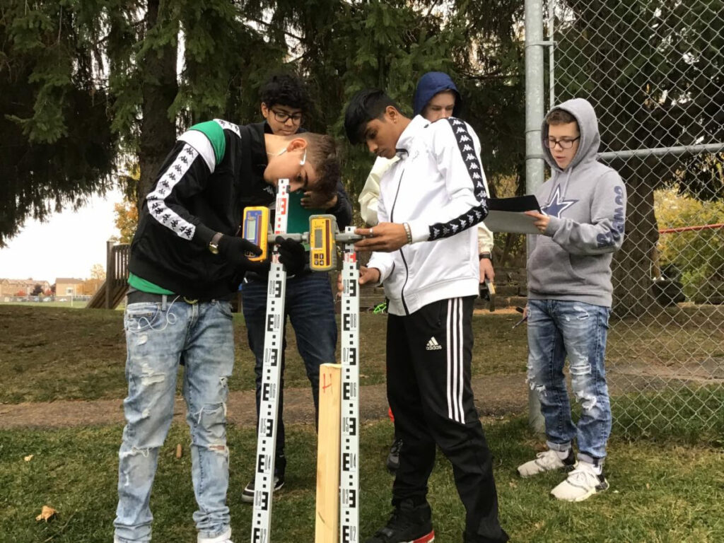 Two students measuring wooden stakes.