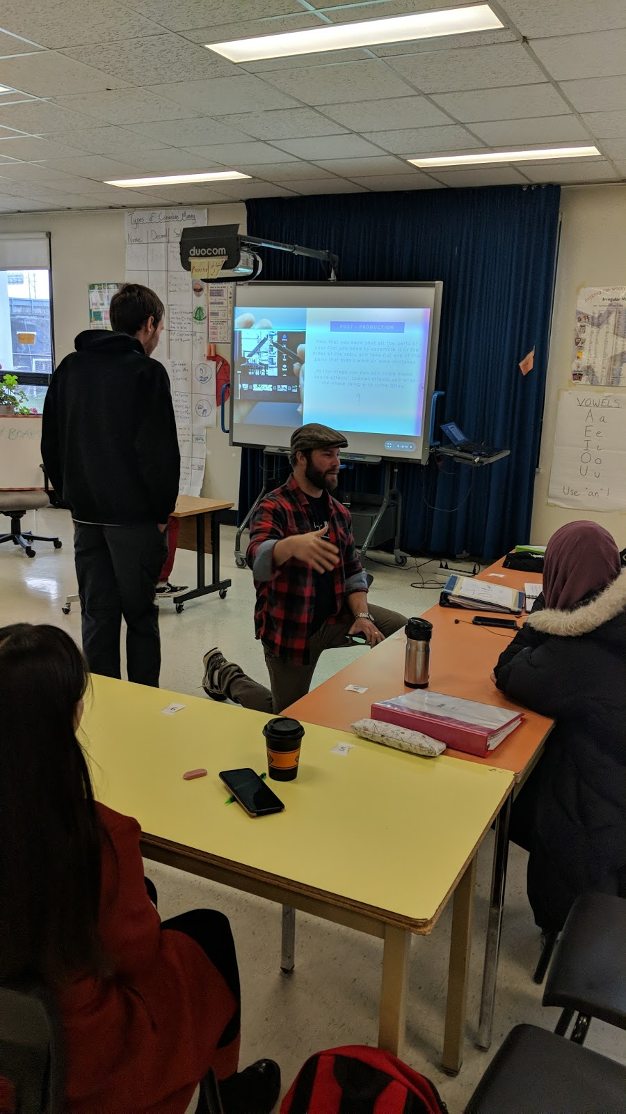 Adults students in a classroom working on a movie.