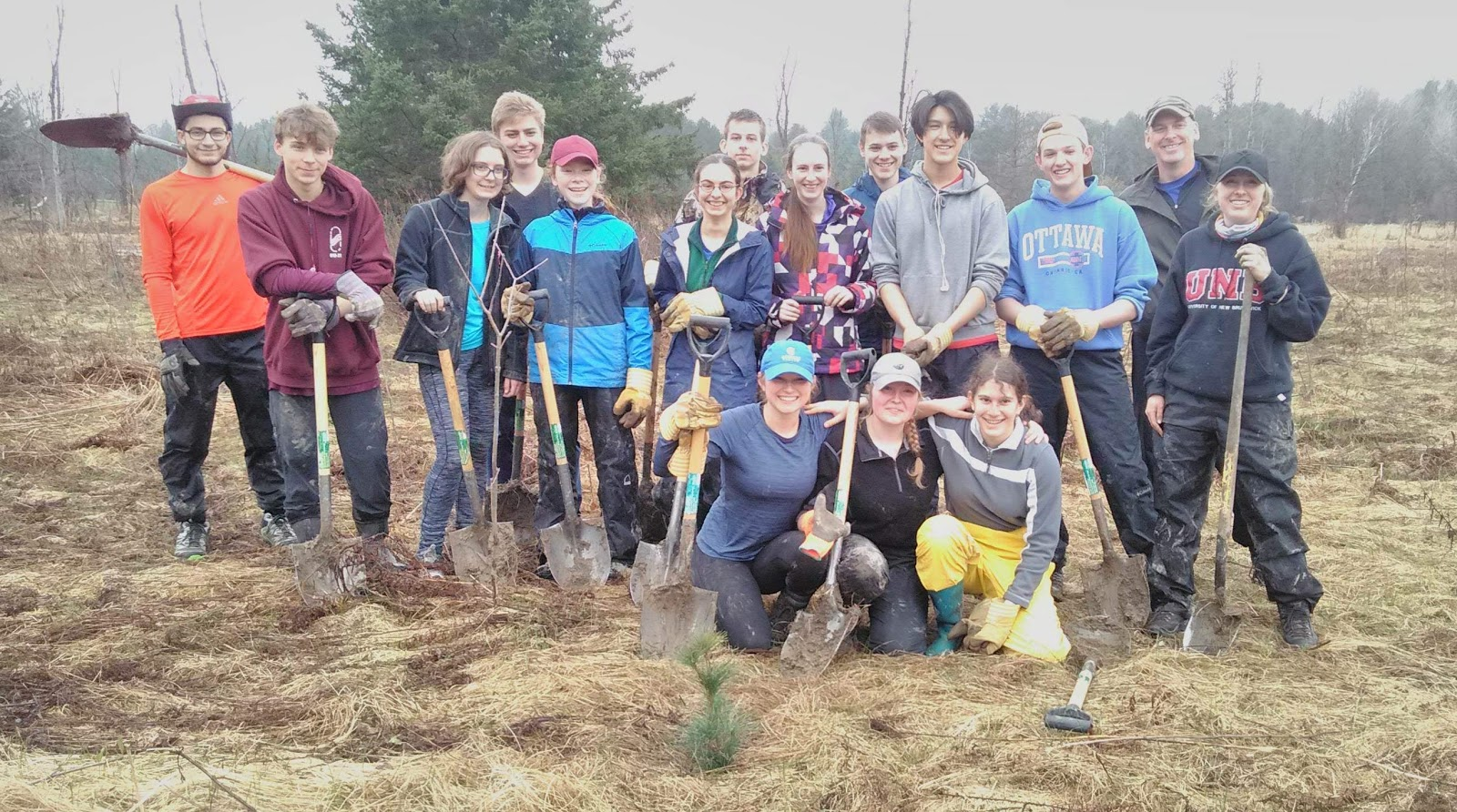 A group of students holding shovels out in nature.