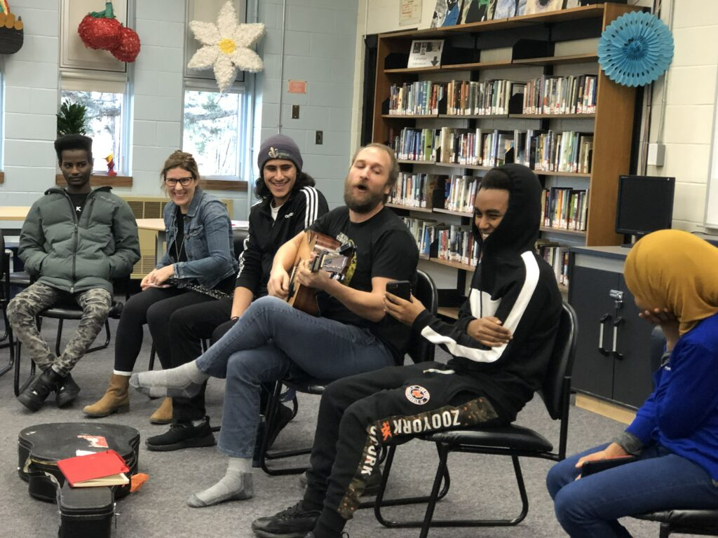 Man plays guitar in circle with a group of students.