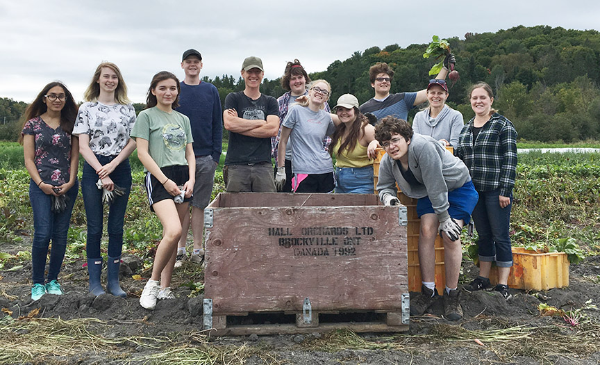 Students stand in a field of produce.