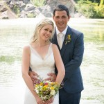 Groom stands behind bride with colorful wedding flowers