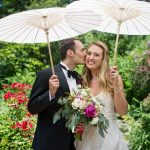Bride and groom holding parasols while groom kisses bride on cheek