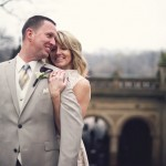 Bride stands behind groom with Bethesda Arcade in background