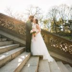 Bride and groom posing on steps of Bethesda Fountain Central Park