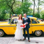 Bride and Groom posing with British flag in front of Vintage NYC Taxi