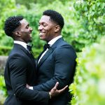 Two grooms hugging by trees in Central Park