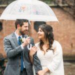 Bride and groom under umbrella at Conservatory Garden