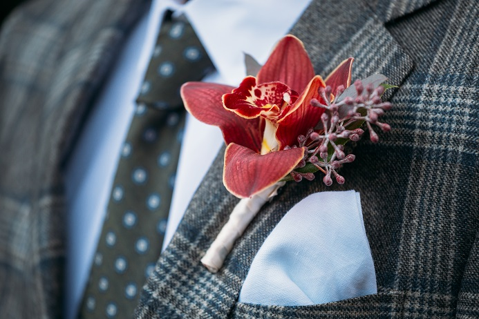 red orchid boutonniere with seeded eucalyptus