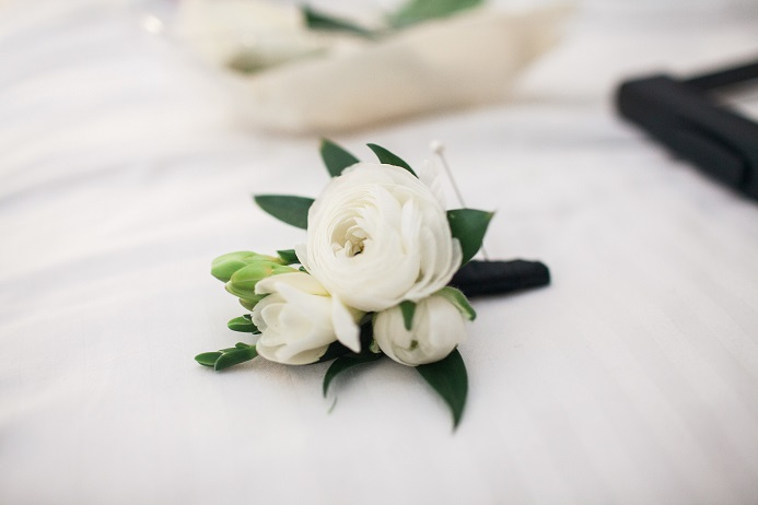White ranunculus and freesia boutonniere