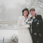 Two brides in Central Park with Bow Bridge in background during snowstorm