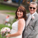 Groom with sunglasses laughs with bride in Central Park