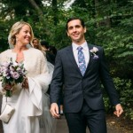 Bride holding bouquet walks with groom in Central Park