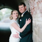Wedding couple hugs leaning on archway in Central Park