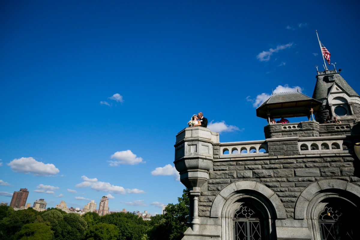 Bride and groom kiss on top of Belvedere Castle against a blue sky
