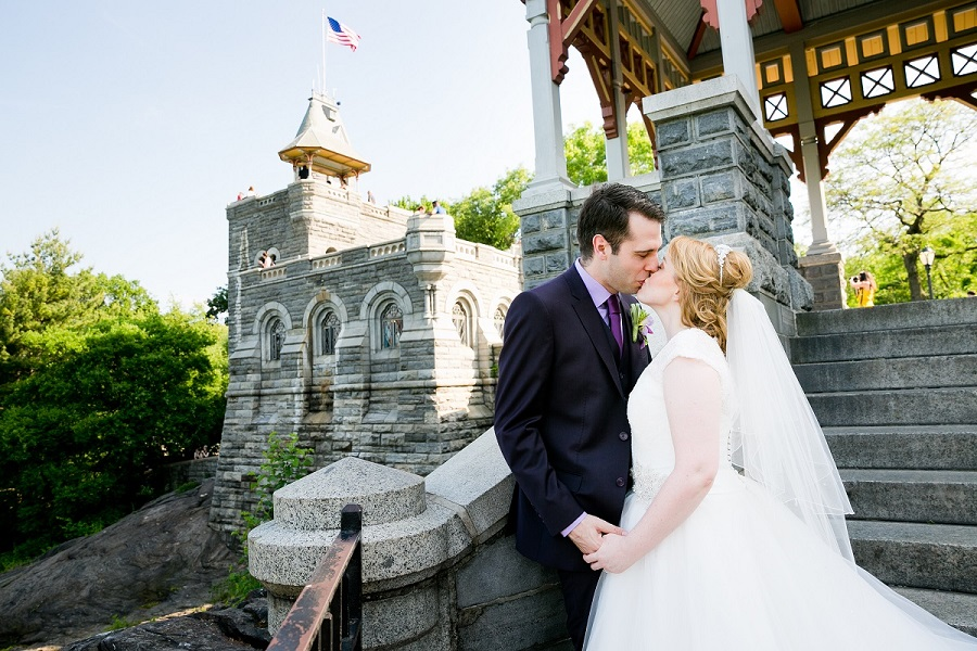 Newlyweds kissing with Belvedere Castle tower in background