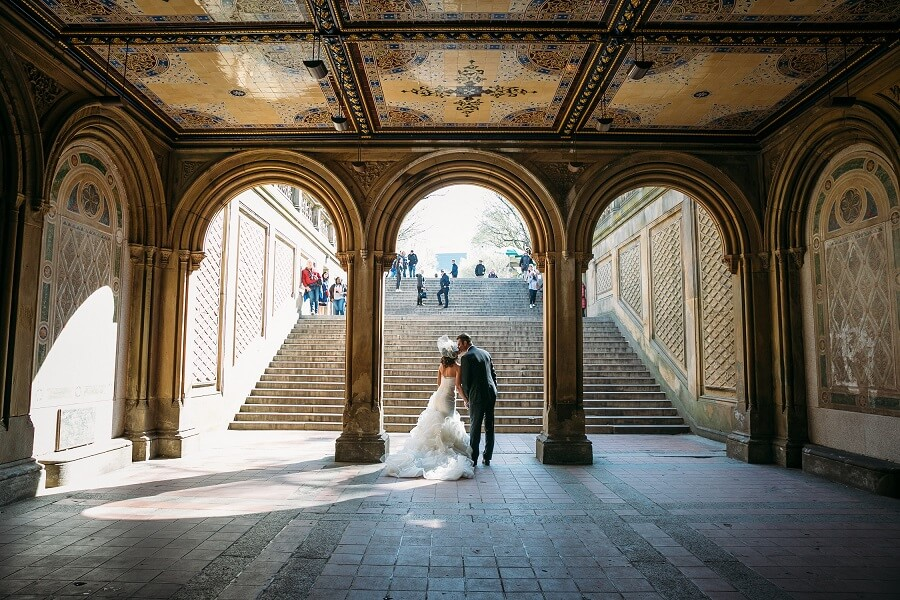 Bride and groom kiss under the archway of Bethesda Fountain