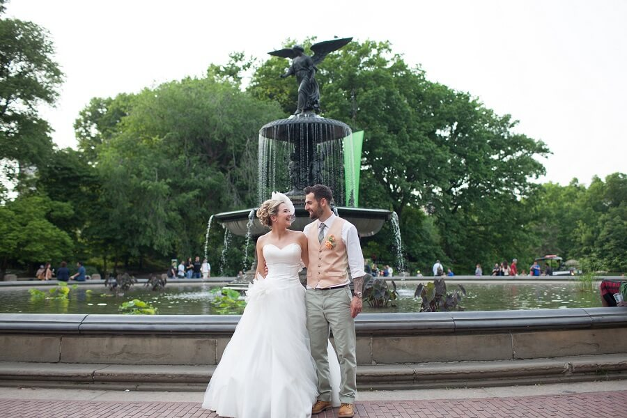Bride and groom smile at each other in front of Bethesda Fountain