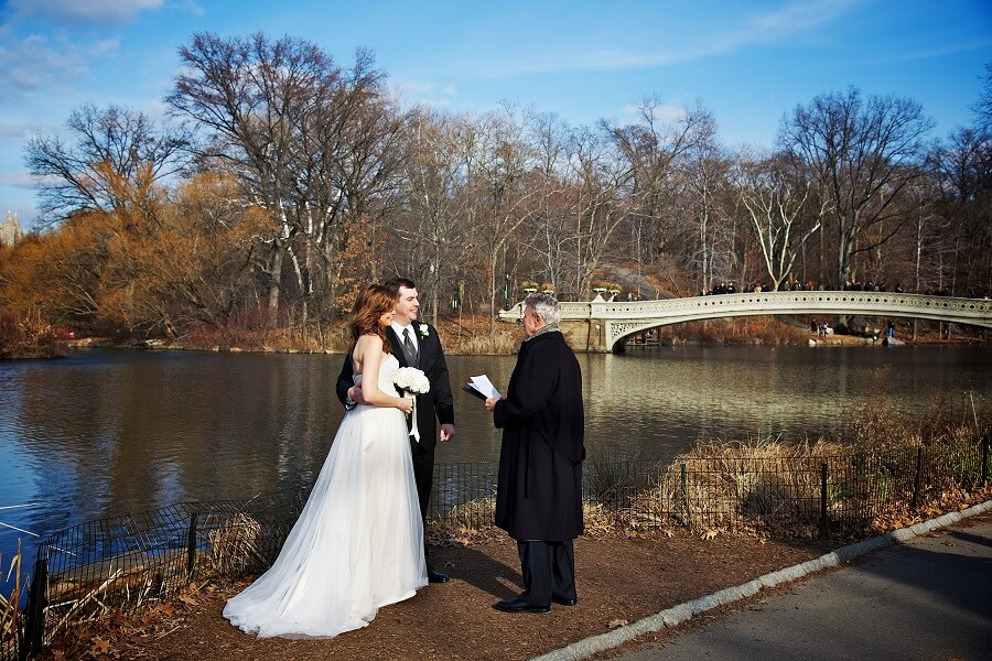 Couple has intimate wedding along Lake with Bow Bridge in background