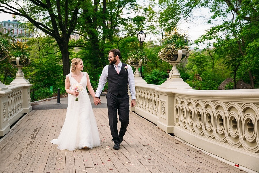 Bridge and groom walk along Bow Bridge holding hands in Spring