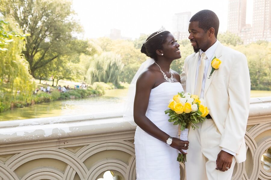 Bride holding bouquet of yellow roses smiles at groom on Bow Bridge