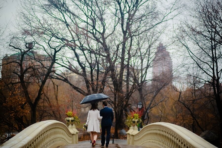 Newlyweds walk away on Bow Bridge holding umbrella