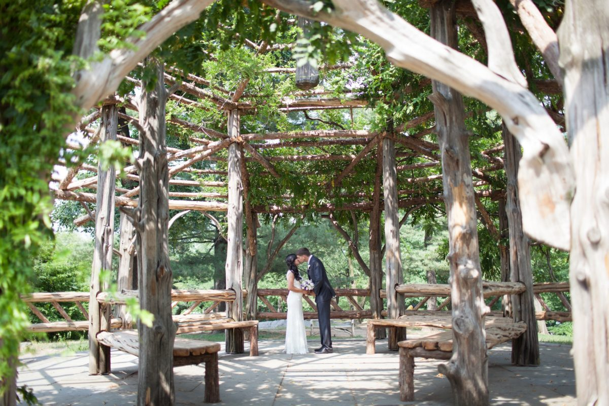 NYC Outdoor Wedding Venues & Locations: Bride and groom kiss inside empty Cop Cot gazebo