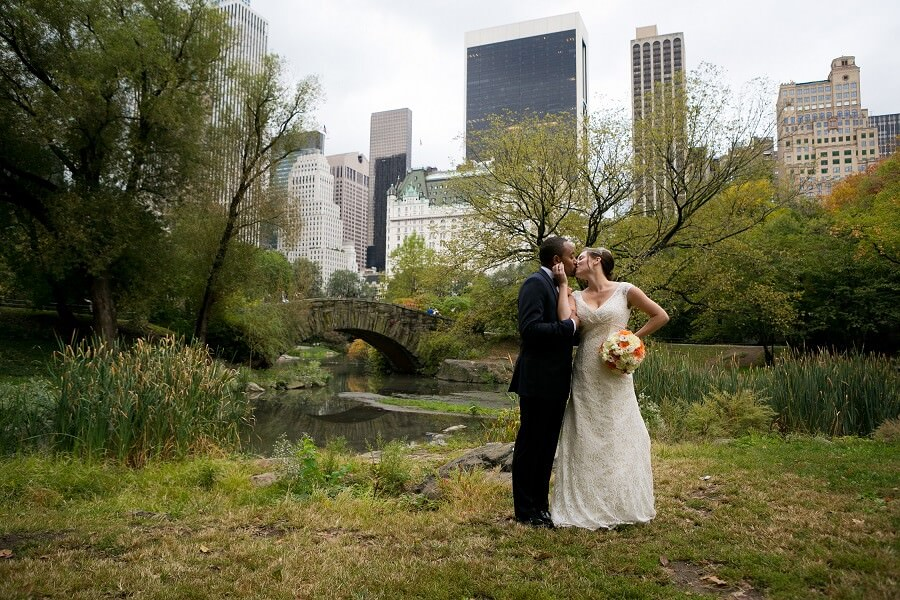 Bride and groom pose behind Gapstow Bridge in Central Park