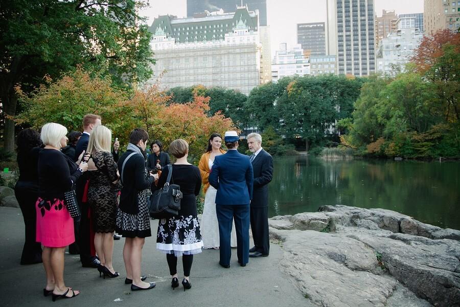 Intimate lesbian wedding ceremony along Pond with NYC skyline