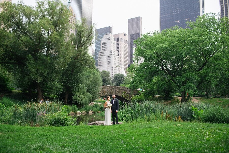 Wide shot of bride and groom posing behind Gapstow Bridge in Spring
