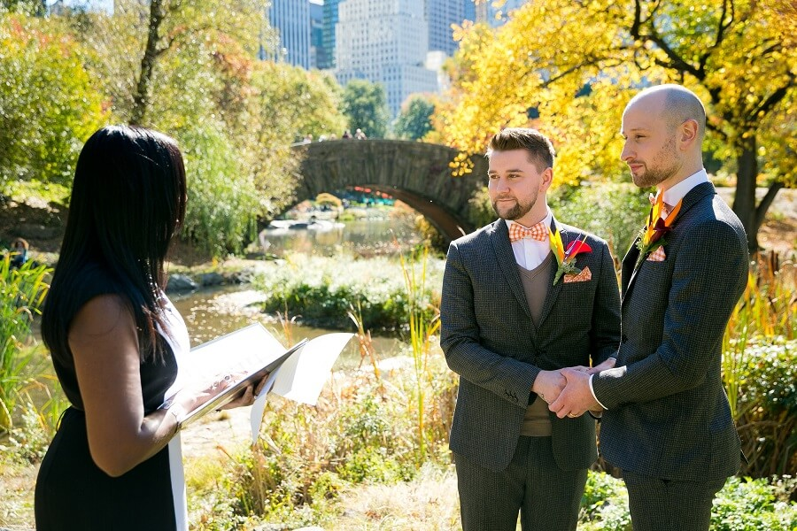 Two men getting married behind Gapstow Bridge in the Fall