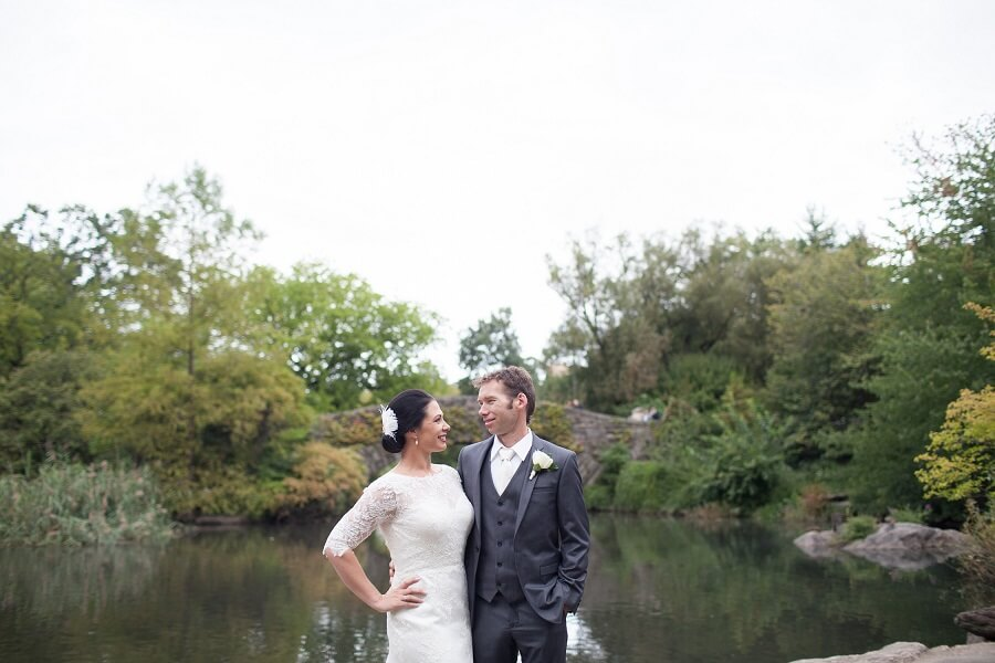 Newlyweds pose in front of Gapstow Bridge in the spring