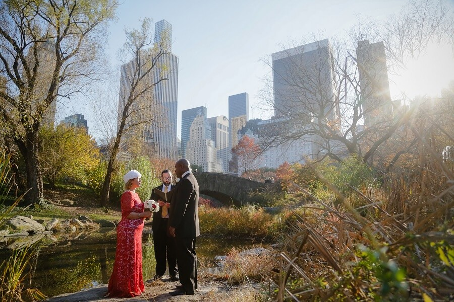 Fall elopement behind Gapstow Bridge with NYC skyline in background