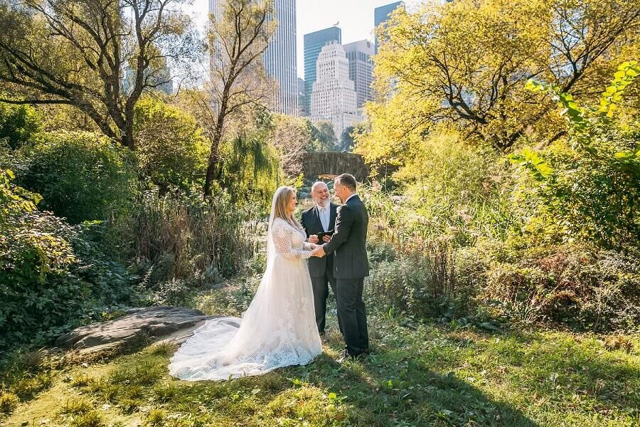 Couple exchanges vows behind Gapstow Bridge in early Fall