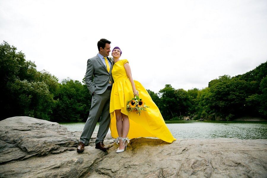 Bride in yellow wedding dress with groom standing next to The Lake