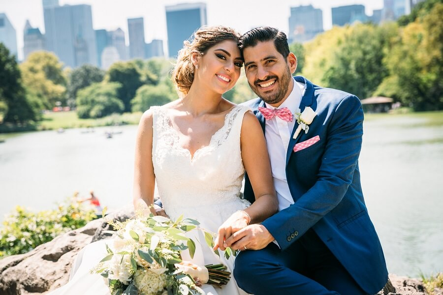 Newlyweds smiling with the NYC skyline in the background