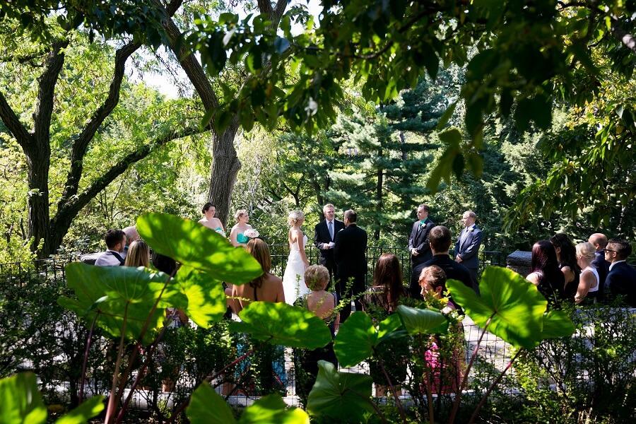 Wedding ceremony at Shakespeare Garden seen through trees