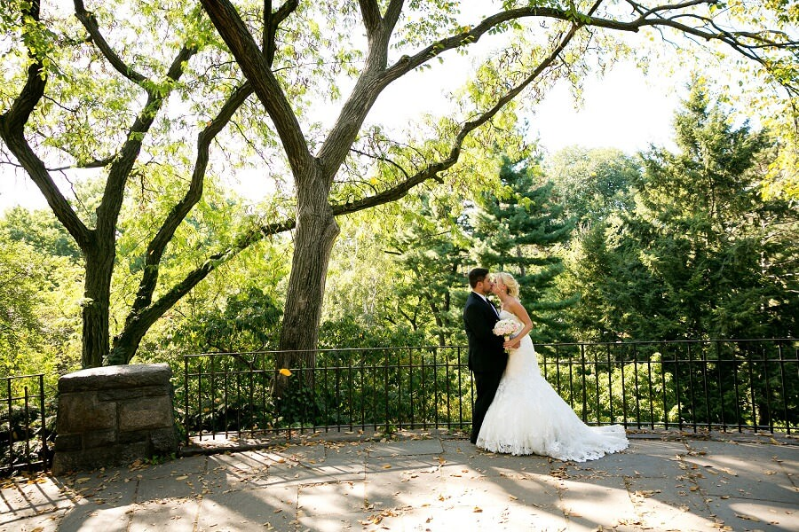 Newlyweds kiss in front of large tree at Shakespeare Garden