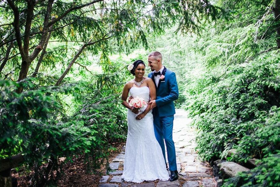 Groom in blue tuxedo and bride smiling in Shakespeare Garden
