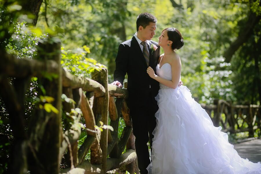Bride and groom against wooden railing in Shakespeare Garden