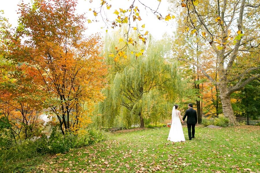 Wedding couple walking through fall foliage along The Pool in Central Park