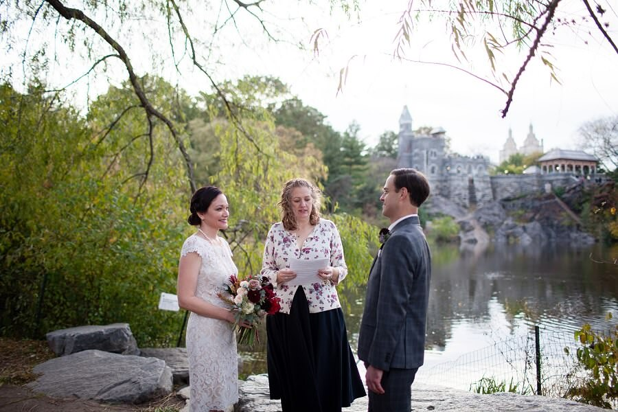 Couple exchanges vows along Turtle Pond with Belvedere Castle in background