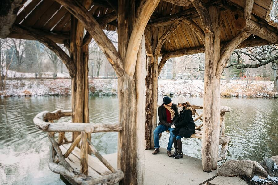 Couple sits on bench at Wagner Cove gazebo in winter