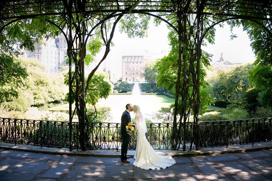 Newlyweds kiss in archway of Wisteria Pergola