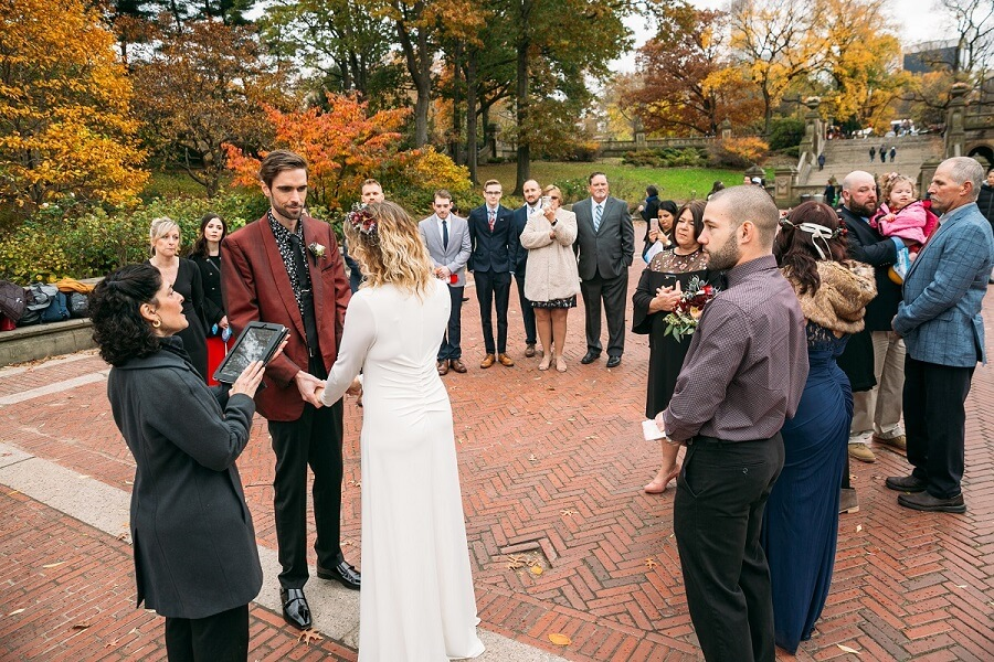 Couple exchanges wedding vows on fall day at Bethesda Fountain