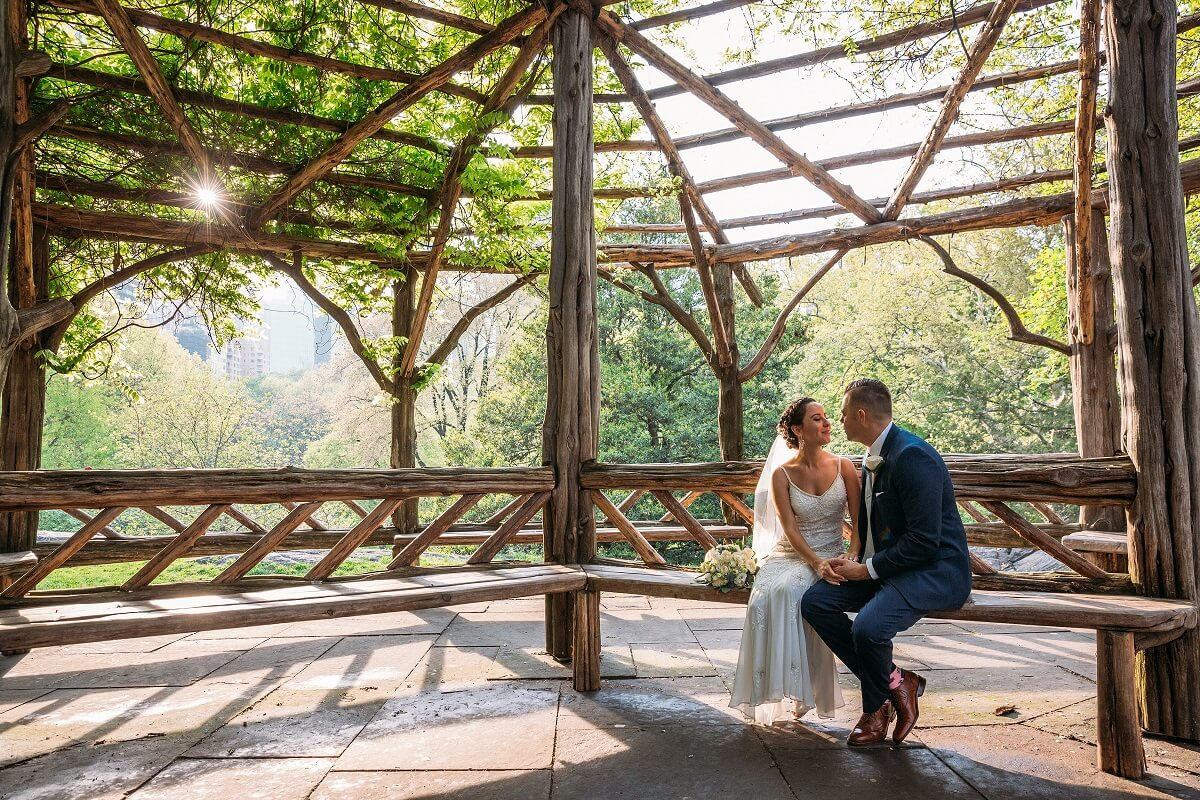 NYC Outdoor Wedding Venues & Locations: Newlyweds pose on Cop Cot bench in Central Park